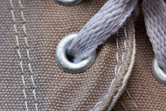 Eyelet tab of canvas shoe, with shoelace, close-up Royalty Free Stock Images