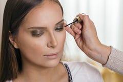 Αποτελέστε τον καλλιτέχνη ισχύοντα eyeliner στα βλέφαρα του πελάτη στοκ φωτογραφία