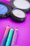Eyepencils et fards à paupières sur le fond pourpré Photographie stock