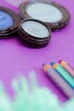 Eyepencils et fards à paupières sur le pourpre avec des pétales Photographie stock libre de droits