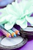 Eyepencils et fards à paupières sur le pourpre avec des pétales Photos stock