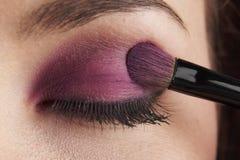 Eyes. Woman applying eye make-up with brush on white background Stock Photography
