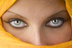 The eyes. Attactive and strong eyes behind an orange scarf used like a burka Stock Photography