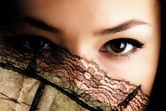 Eyes. Female eyes behind flabellum, close up, studio Royalty Free Stock Photography