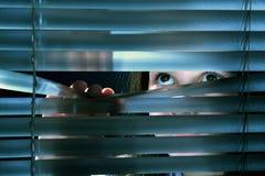 Eyes. Girl's eyes looking through window blinds Stock Image