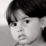 Eyes As Black As Coal. Face of a little girl with large eyes and rosebud shaped lips.. In monochrome Royalty Free Stock Photo