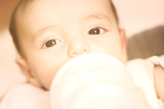 Eyes of a baby while drinking milk  selective focus warm filter Stock Photo