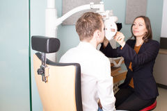 Eyes being checked at store with optician. Optician preparing an eye exam Royalty Free Stock Photo
