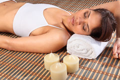 Eyes closed in health spa lying on bamboo mat. Beautiful young woman in a spa lying on a bamboo mat. Model wearing white vest, has head resting on white towel royalty free stock images