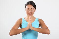 Eyes closed meditating beautiful young woman. Beautiful young woman with eyes closed and hands together in calm meditating pose during exercise routine. Studio stock photography