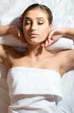 Eyes closed relaxing beautiful young woman lying on her back and getting beauty massage enjoying treatment having fun on white Royalty Free Stock Photo