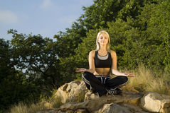 Eyes closed woman meditating yoga on rock Royalty Free Stock Image