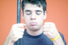 Eyes Closed - Young Male. Young man stands with eyes closed and fists clenched shut. One fist closed over a pole. Orange background stock image