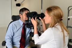 Eyes del doctor Examining Man's Imagenes de archivo