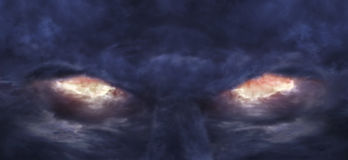 Eyes of the devil. A picture of stormy clouds that formed the image of scary devil face Royalty Free Stock Images