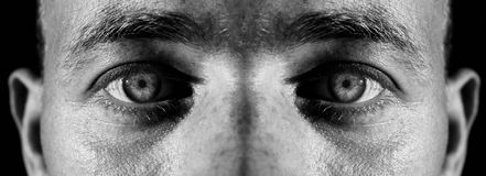 Eyes evil stare. Eyes or iris of male closeup stare or look at camera. monochrome image of face and skin Stock Photos