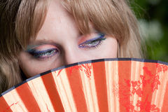 Eyes and a fan Stock Photography