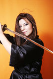 Eyes on the foe. Swings a sword, hair swooshes, eyes intent Stock Image