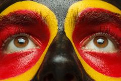 Eyes of German or Belgian sports fan patriot. Painted country flag on man face. Stock Photo