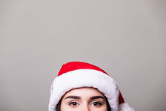 Eyes of girl in santa hat on grey background. Stock Photography