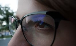 eyes of the girl wearing glasses in a black frame stock photo