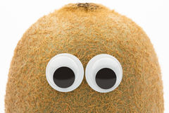 Eyes on kiwi. Kiwi fruit with toy eyes on white Royalty Free Stock Photo