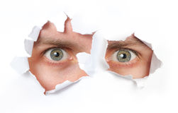 Eyes looking through a hole. In a paper isolated Stock Photo
