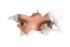 Eyes looking through a hole in paper. Eyes looking through a hole in a paper Royalty Free Stock Image