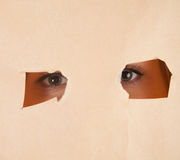 Eyes looking through a holes in a paper Stock Image