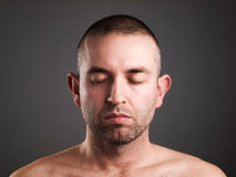 Eyes man closed on dark background. He is caucasian stock image