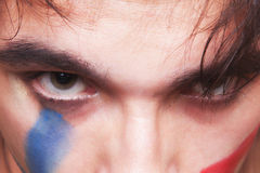 Eyes of  man with the red and blue paint Stock Images