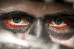 Eyes of a man wearing skull makeup. With bloodshot rims and deep shadowed eye sockets looking at the camera over the blade of a knife, Halloween horror concept royalty free stock photos