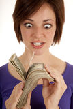 Eyes money. A woman with a greedy expression on her face fanning her money in front of her Royalty Free Stock Images