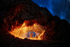 Eyes are painted burning steel wool in the mountain. Burning Steel Wool spinning. Showers of glowing sparks from spinning steel wool Royalty Free Stock Photo