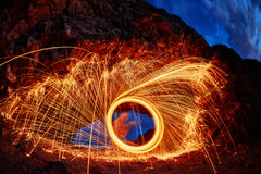 Eyes are painted burning steel wool in the mountain. Burning Steel Wool spinning. Showers of glowing sparks from spinning steel wool Stock Photo