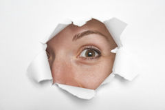 Eyes through paper. Revealing paper;business concepts; eyes through broken paper Stock Photo