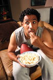 Eyes Popping. A man holding a football eating popcorn looking very surprised Royalty Free Stock Photo