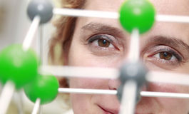 The Eyes Of A Researcher. Image of a female researcher eye through a molecular model structure.Selective focus on the eye Royalty Free Stock Photo