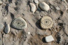 Eyes sand. Eye - drawn on pebble on a beach royalty free stock photo