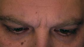 Eyes of serious frowning caucasian man using his tablet computer. Screen reflecting in the eyes, device lighting glow stock footage