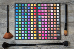 Eyes shadows palette. Maquillage. Set of brushes on wooden table Royalty Free Stock Photo