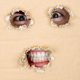 Eyes and teeth look out from hole Royalty Free Stock Image