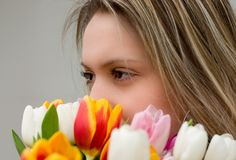 Eyes and tulips. Obverse portrait of the young girl with a bouquet of tulips Royalty Free Stock Images