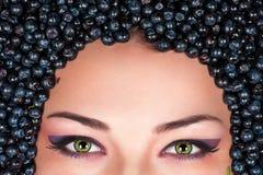 Eyes of woman lying in blueberries. Beautiful eyes of woman lying in blueberries Royalty Free Stock Image