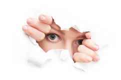Eyes of woman peeking through a hole torn in white paper poster. Eyes of a young curious woman peeking through a hole torn in white paper poster stock photo