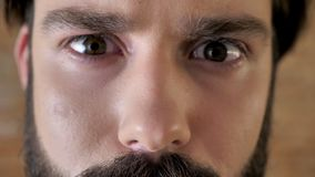 Eyes of young serious man with mustache, sadness, watching at camera.  stock video