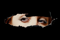 Eyes of a young woman peeping through hole Royalty Free Stock Image