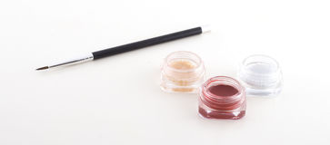 Eyeshadow. A brush and different coloured eyeshadows in front of white background Stock Photography