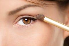 Женщина состава глаза прикладывая порошок eyeshadow Стоковое фото RF