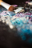 Eyeshadow make-up powder and brush, shallow dof. A still-life of colourful eyeshadow powder and make-up brush Royalty Free Stock Image